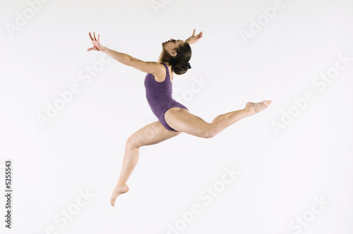 Gymnast 13-15 leaping in air, side view