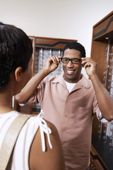Man trying on glasses at opticians