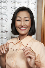 Woman trying on glasses at opticians, portrait