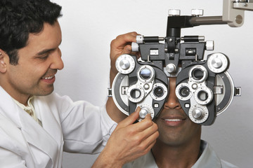 Optician performing eye test on patient