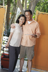 Holidaymaker couple standing at gate holding suitcase and brochure, portrait