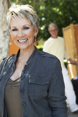 Elegant mature woman smiling, standing outdoors