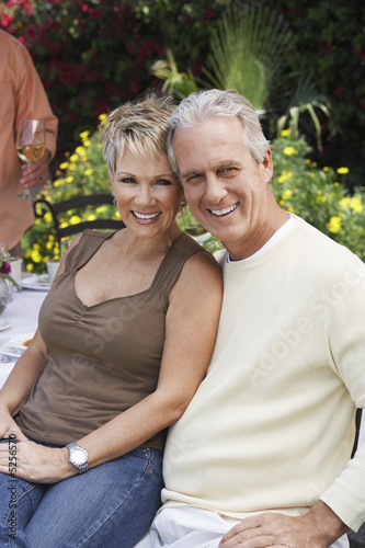 Affectionate middle aged couple sitting outdoors