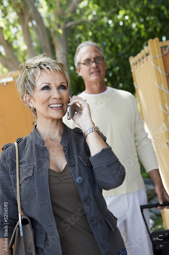 Mature woman using mobile phone walking through gate with husband