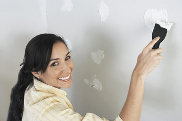 Woman speckling interior wall, elevated view