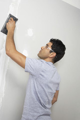 Man sanding interior wall