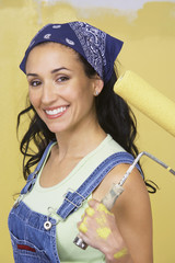 Woman holding paint roller, portrait