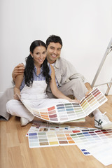 Couple looking at paint colour samples, sitting on floor, portrait