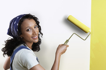 Woman painting wall yellow, portrait