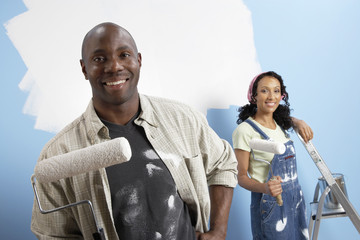 Couple holding paint rollers, portrait
