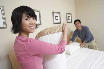 Couple making bed together, portrait