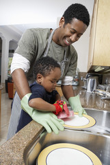 Son 3-6 helping father wash dishes