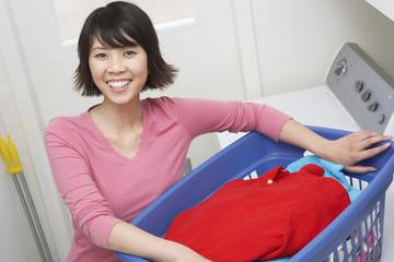 Woman holding laundry basket, portrait