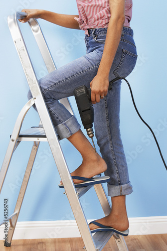 Woman holding power drill on stepladder, low section