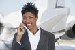 Smiling Businesswoman standing outside Airplane, talking on mobile