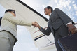 Businesswomen Shaking Hands below airplane wing, low angle view