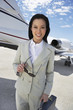 Businesswoman Beside an Airplane, holding sunglasses, low angle view