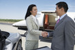 Business People standing near sports car and private airplane, Shaking Hands, side view