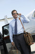 Smiling businessman standing beside car near private jet, talking on mobile before Leaving on Business Trip