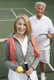 Smiling Couple standing on Tennis Court, holding rackets and ball