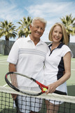 Smiling Couple standing on Tennis Court, arms around, holding rackets