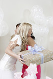 Bride holding gift, Hugging friend at Bridal Shower, side view