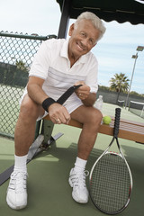 Tennis Player sitting on bench near tennis court Wrapping His Wrist Supporter