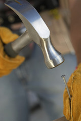 Construction Worker wearing leather gloves, hammering nail, close-up