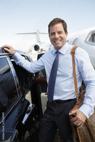 Smiling businessman standing beside car near private jet before Leaving on Business Trip