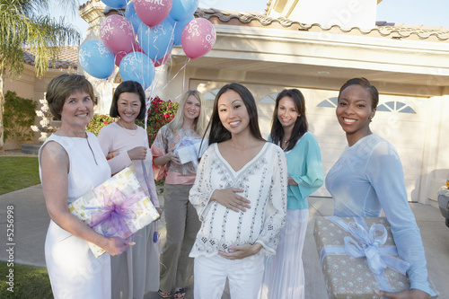 Group of friends with gifts for baby shower outside house