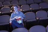 Man sitting alone in empty theatre eating popcorn, Watching Movie