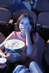 Young woman holding Popcorn, covering face with hand, watching movie in Theatre