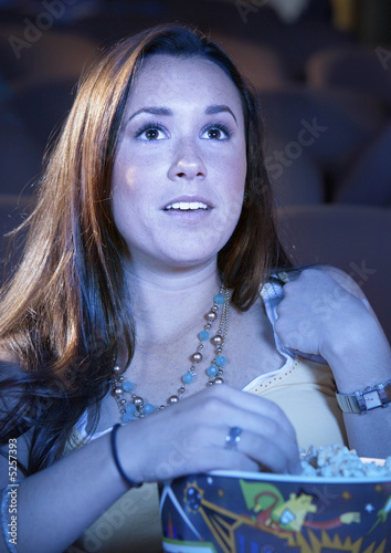 Young woman Eating Popcorn, watching movie in Theatre