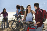 Group of young adults standing by lake with mountain bikes.