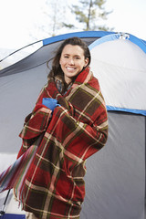 Young woman wrapped in blanket and holding mug, standing in front of tent
