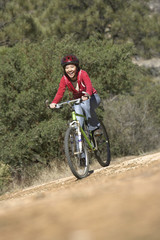 Young Woman Mountain Biking in field
