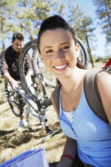 Young woman sitting outdoors, man repairing mountain bike in background, portrait.