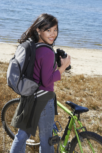 Young woman standing with mountain bike using binoculars by lake