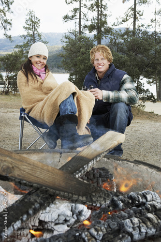 Young couple in warm clothing, sitting by campfire