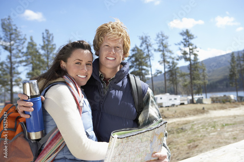 Young couple hugging at campground, holding thermos and map.