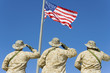 Rear view of  three U.S military personnel saluting the American flag against bright blue sky
