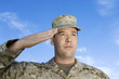 Soldier saluting against sky, close-up