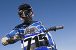 Motocross racer on bike against blue sky, low angle view