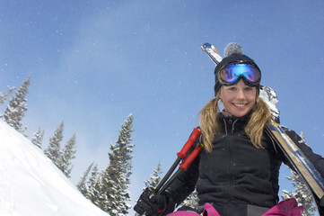 Teenage girl 16-17 holding skis, in front of snow covered hill