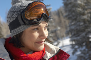 Young woman wearing ski goggles on head in snow, portrait.