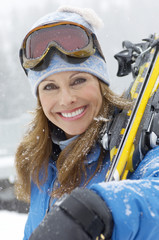Woman holding skis in snow, head and shoulders, portrait.