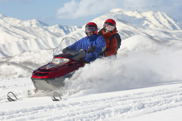 Couple driving snowmobile in front of snow covered mountains