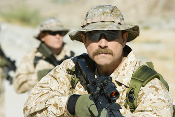 Soldier carrying rifle, outdoors