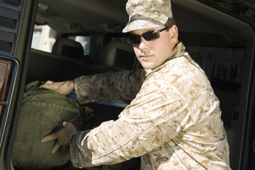 Soldier loading bag into vehicle, portrait
