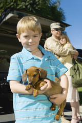 Boy 5-6 holding dog, outdoors, portrait